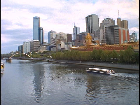 A boat glides down the river with the skyline of... Stock Video Footage