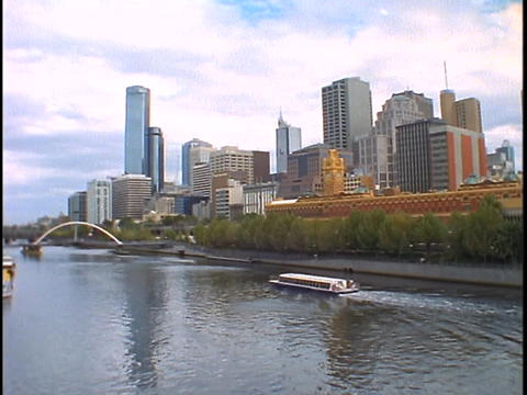 A boat glides down the river with the skyline of Melbourne, Australia in the distance Footage