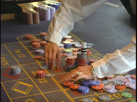 A gaming professional lays chips out on a gaming table Stock Video Footage