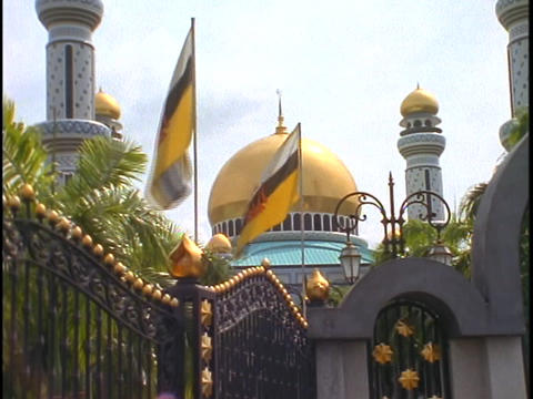 Flags wave in the breeze in front of the Gold palace of Sultan of Brunei in Borneo Live Action