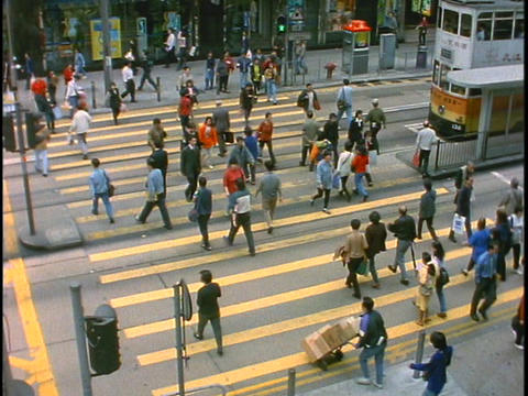 Pedestrians cross a busy intersection in China Footage