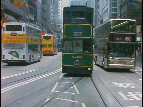 Buses pass on the streets of Hong Kong, China Live Action