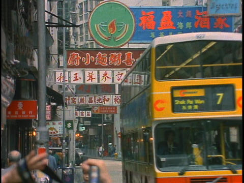 A double decker bus passes other traffic on a busy downtown street in Hong Kong, China Footage