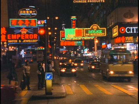 Pedestrians and car traffic move along a busy street in... Stock Video Footage