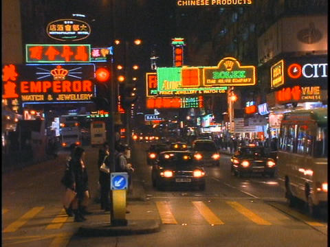 Pedestrians and car traffic move along a busy street in Hong Kong Footage