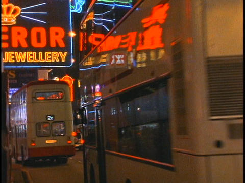 Double-decker buses drive on a busy street in Hong Kong... Stock Video Footage