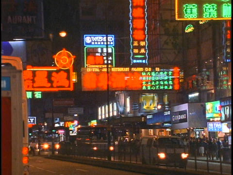 Traffic and pedestrians move along a busy street in Hong Kong at night Footage