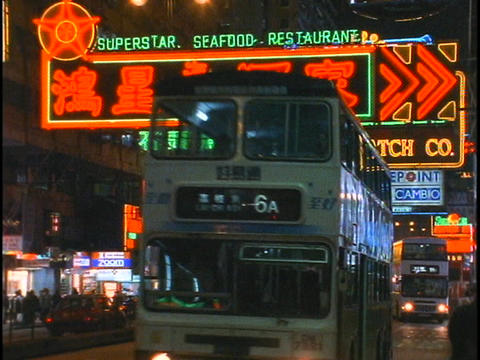 Bus, car and pedestrian traffic pass by on a busy street in Hong Kong at night Footage