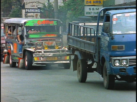 A jeepney drives in heavy traffic down a street in... Stock Video Footage
