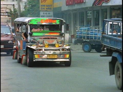 A jeepney drives in heavy traffic down a street in... Stock Video Footage