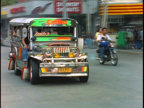A jeepney drives in heavy traffic down a street in Manila, Philippines Footage