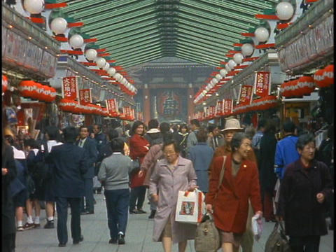 Shoppers walk through a shopping mall near a Buddhist Temple in Tokyo, Japan Footage