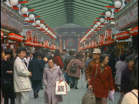 Shoppers walk through a shopping mall near a Buddhist... Stock Video Footage