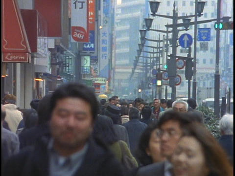 Crowds of pedestrians walk along a street in the Ginza District of Tokyo, Japan Footage