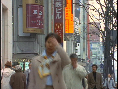 Crowds of pedestrians walk down a street in the Ginza District of Tokyo, Japan Footage