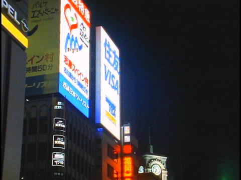 Streaming billboards light up the sides of buildings in... Stock Video Footage