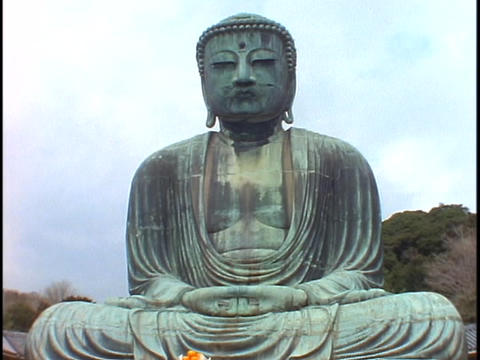 A giant Buddha statue sits in a garden in Kamakura, Japan Footage