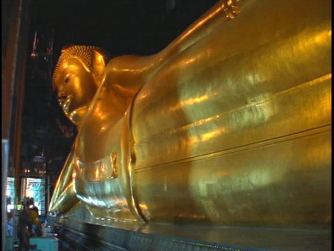 A golden Buddha statue sits in a temple in Bangkok, Thailand Live Action