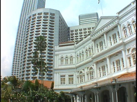 The skyline of Singapore rises above the Raffles Hotel in... Stock Video Footage