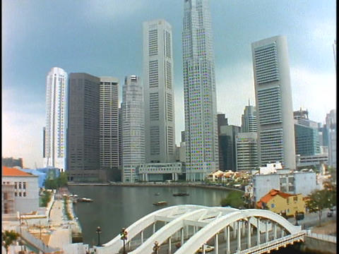 The skyline of Singapore rises above a bridge spanning a... Stock Video Footage