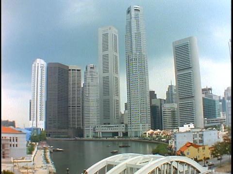 The skyline of Singapore rises above a bridge spanning a harbor Footage