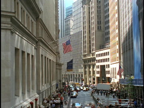 Pedestrians and cars travel down Wall Street in New York... Stock Video Footage