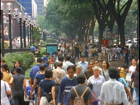 Crowds of people walk down a sidewalk in the Orchard Road district of Singapore Footage