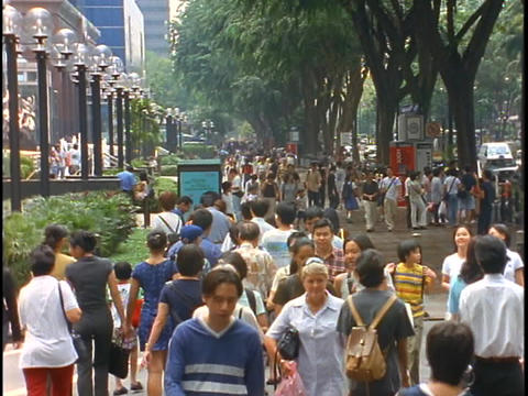 Crowds of people walk down a sidewalk in the Orchard Road... Stock Video Footage
