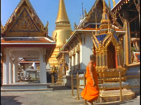 A Buddhist monk in orange robes walks out of a Buddhist... Stock Video Footage