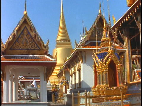 A Buddhist monk in orange robes walks out of a Buddhist temple with a golden spire in Bangkok, Thail Footage