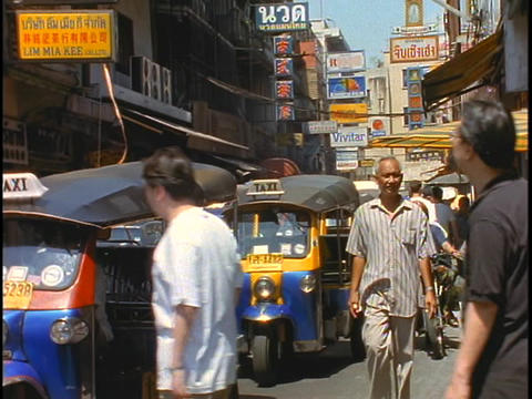 Pedestrians walk past Tuk-tuk taxis idling on a street in... Stock Video Footage