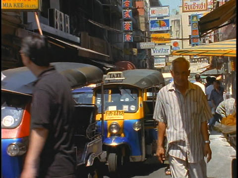 Pedestrians walk past Tuk-tuk taxis idling on a street in Bangkok, Thailand Footage