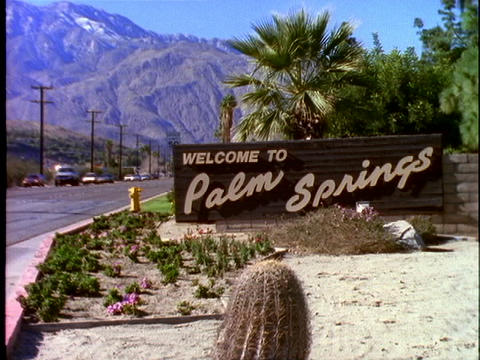 Traffic drives past the town sign for Palm Springs, California Footage