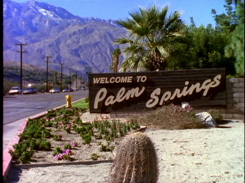 Traffic drives past the town sign for Palm Springs,... Stock Video Footage