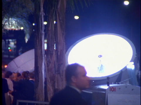 A crowd of people mill around two rotating spotlights at... Stock Video Footage