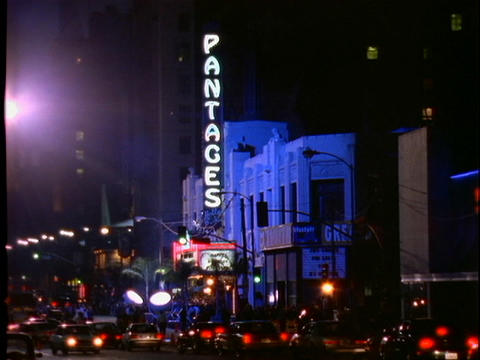 Traffic slowly passes the Pantages movie theater which is... Stock Video Footage