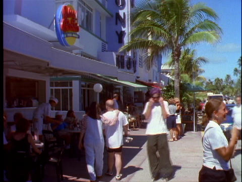 Pedestrians walk past people eating on outdoor tables at... Stock Video Footage