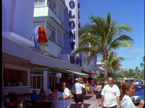 Pedestrians walk past people eating on outdoor tables at a cafe in Miami Beach, Florida Footage