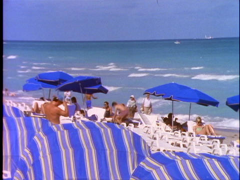 Sunbathers relax under beach umbrellas on Miami Beach Stock Video Footage