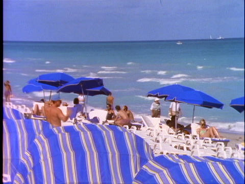 Sunbathers relax under beach umbrellas on Miami Beach Footage
