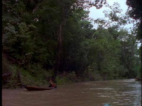 An Amazonian man canoes down the Amazon River in Brazil Footage
