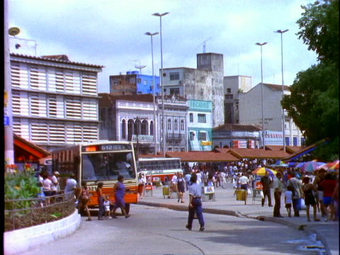 Buses and pedestrians pass by on a busy street in Manaus,... Stock Video Footage