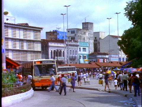 Buses and pedestrians pass by on a busy street in Manaus, Brazil Footage