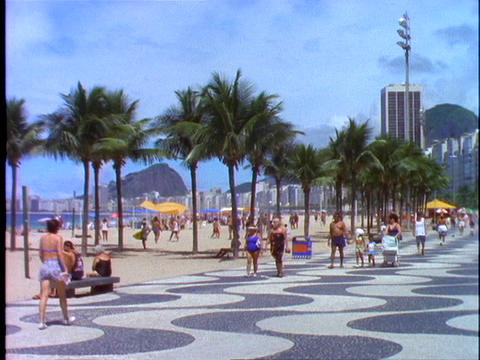 Pedestrians walk down the walkway of Copacabana beach in Rio De Janeiro, Brazil Footage