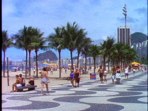 Pedestrians walk down the walkway of Copacabana beach in... Stock Video Footage