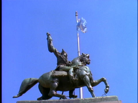 A flag flies behind a statue in Buenos Aires Stock Video Footage