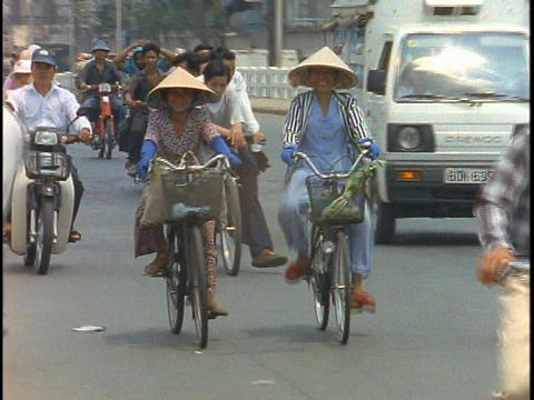 Bike traffic pedals down the streets of Saigon, Vietnam Stock Video Footage