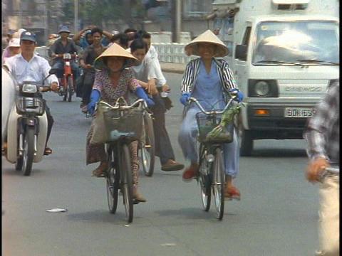 Bike traffic pedals down the streets of Saigon, Vietnam Stock Video Footage