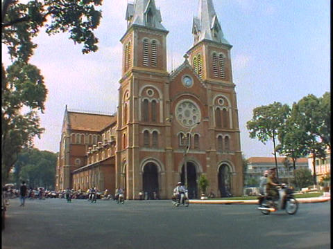 Traffic passes a Catholic Church in Saigon Stock Video Footage