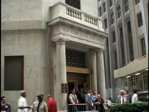 Pedestrians Walk In And Out Of The Entrance Of The New York Stock Exchange stock footage